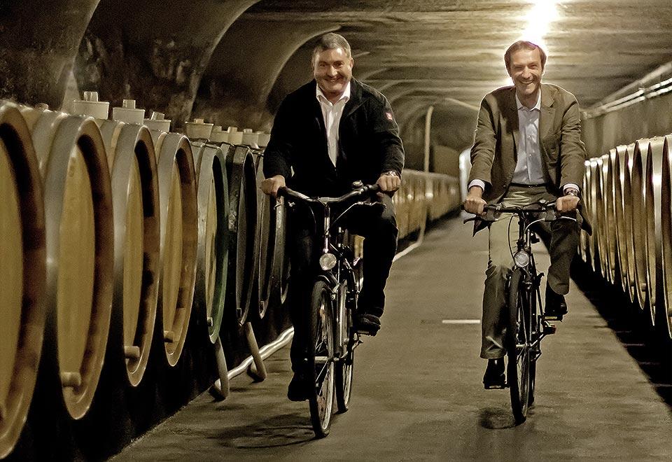 Directeur Dr. Kartsen Weyand und kellermeister Johannes Becker fietsend door de gewelven in Trier